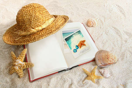 Book with straw hat and seashells at the beach photo