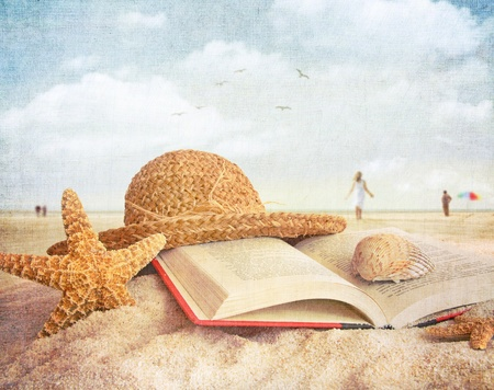 Straw hat , book and seashells on the beach with people walking photo