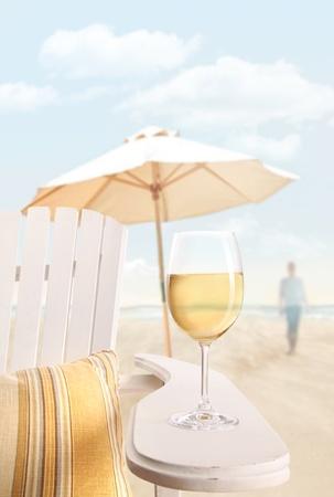 해변에서 adirondack 의자에 화이트 와인의 유리 스톡 콘텐츠