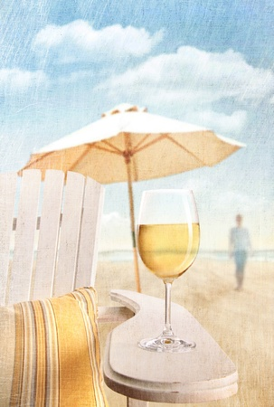 Glass of white wine on adirondack chair at the beach