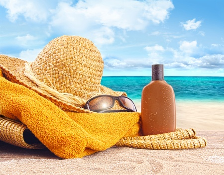 Suntan lotion, straw hat with towel at the beach Stockfoto