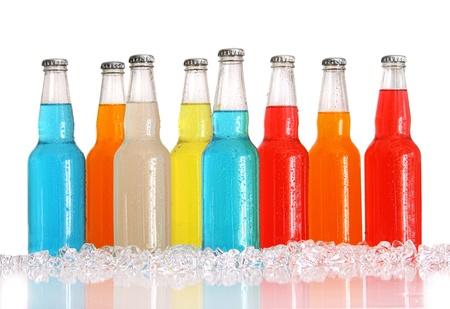 gaseosas: Botellas de bebidas multicolor con hielo sobre fondo blanco