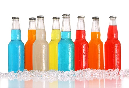 Bottles of multi-color drinks with ice on white background photo