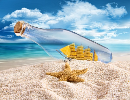 Ship in a bottle lying in the sand photo