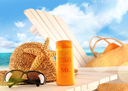 suntan lotion: Sunblock lotion and accessories on table at the beach