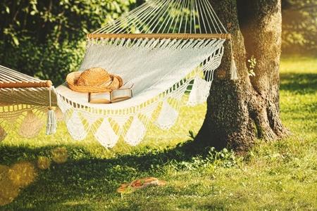 Ansicht der Hängematte und des Buches an einem sonnigen Sommertag Standard-Bild