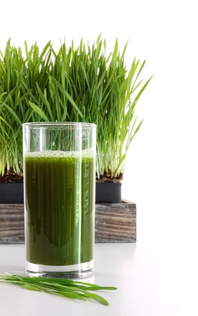 detox: Glass of wheatgrass against a white background