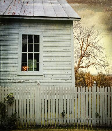 Old farm house with pumpkin in window ready for Halloween