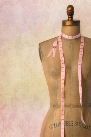 cancer ribbon: Pink breast cancer ribbon on mannequin  dress form with vintage background Stock Photo