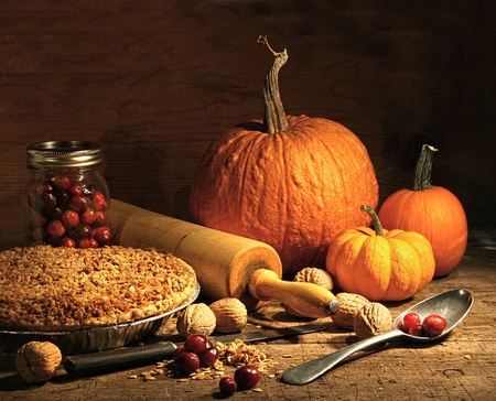 Freshly baked pie with pumpkin, nuts and cranberries on rustic table photo