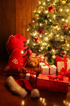 Closeup of brightly lit Christmas tree with gifts