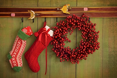 holidays: Christmas stockings and wreath hanging on rustic wall