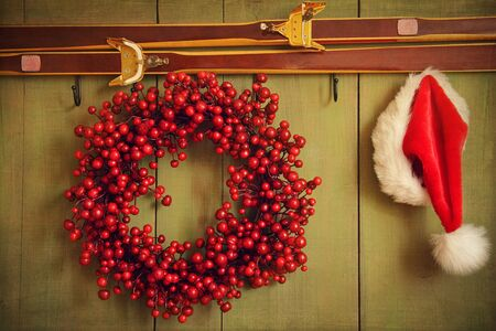 Christmas wreath with Santa hat hanging on rustic wall photo
