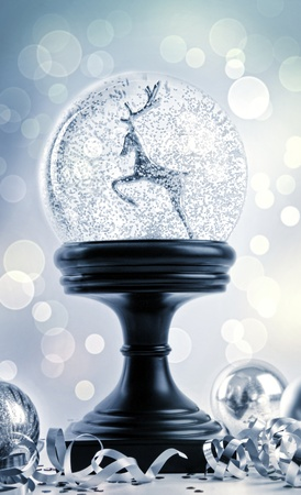 Snow globe with ornaments against a festive background