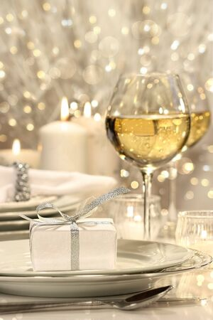 Festive table setting with silver ribbon gift on plate photo