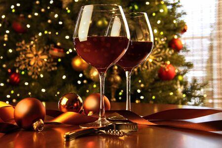バック グラウンドでクリスマス ツリーのテーブルに赤ワイン 写真素材