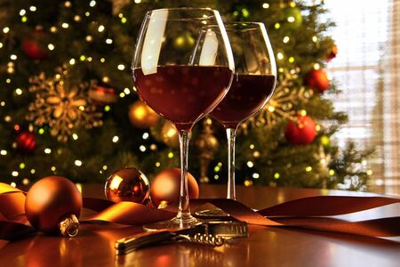 christmas background: Red wine on table Christmas tree in background