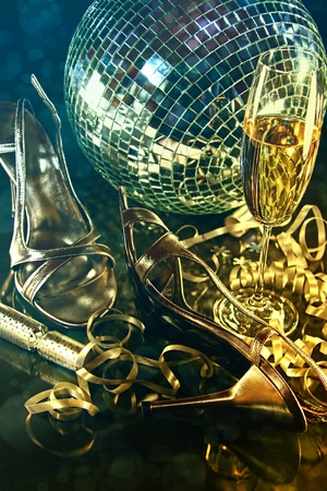 Silver party shoes on floor with champagne glass for New Year photo
