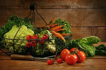 Freshly picked vegetables in metal basket on wooden table 스톡 콘텐츠