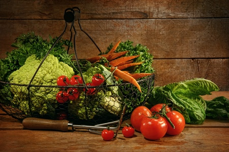 Freshly picked vegetables in metal basket on wooden table Stock Photo