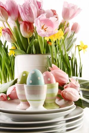 白い背景の春の花とカップのイースターエッグ