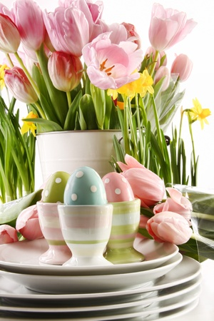 Easter eggs in cups with spring flowers on white background photo