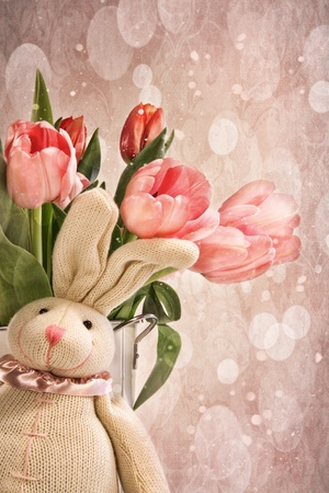 Stuffed rabbit with pink tulips for Easter photo
