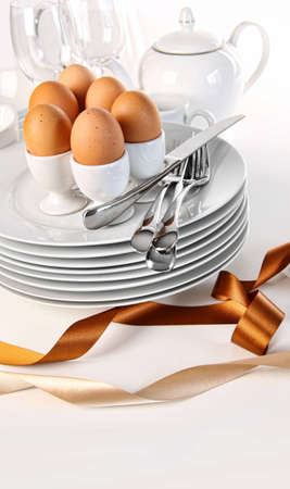 Brown eggs with plates for Easter breakfast on white photo