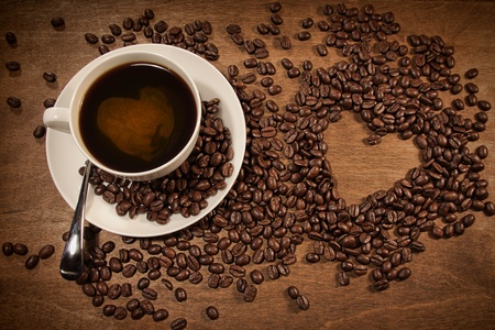 Heart shape from coffee beans on wood background photo