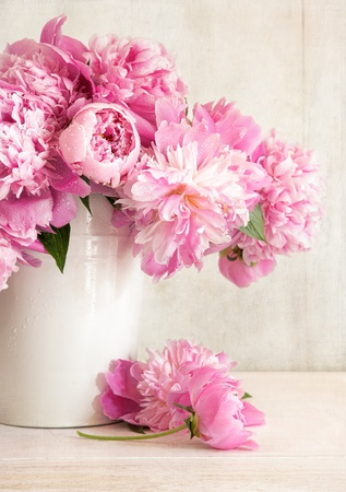 Pink peonies in vase on wood background photo