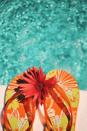 informal clothes: Flip Flops on white towel by swimming pool