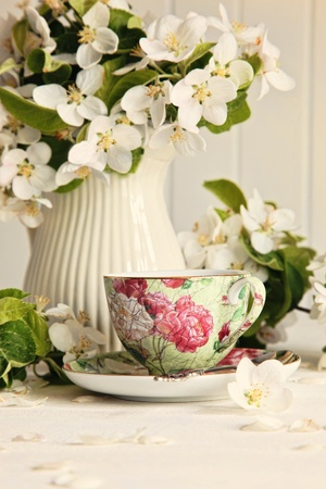 Tea cup with fresh flower blossoms on table