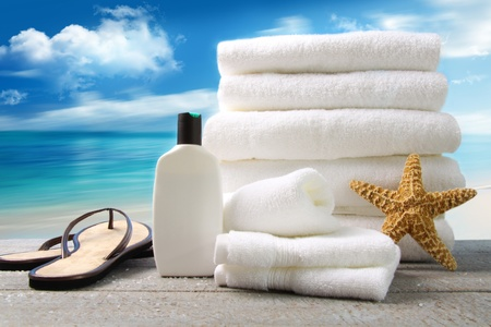 Lotion  towels and sandals with ocean scene photo