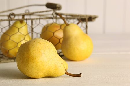 Fresh ripe pears in metal basket on table photo