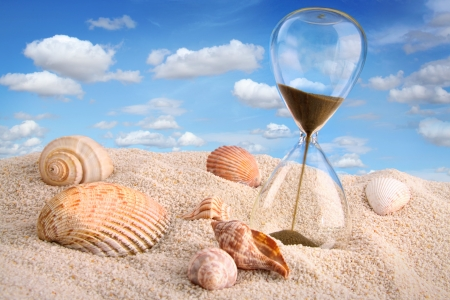 hurry up: Hourglass in the sand with blue sky