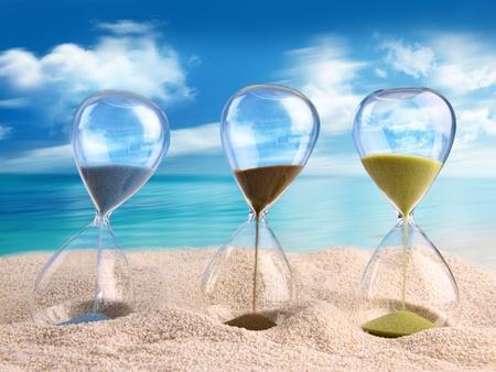 Drie zandloper in het zand met blauwe hemel Stockfoto