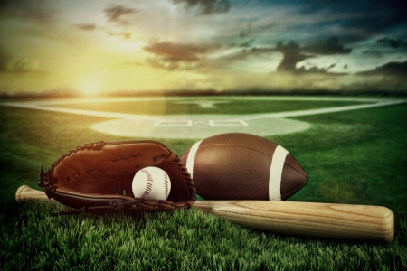 Baseball, bat, and mitt with field in background at sunset