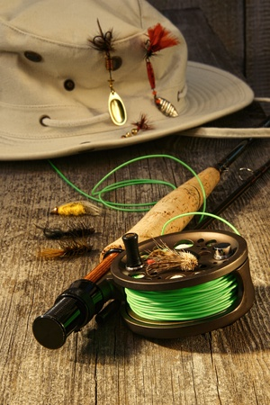 Fishing reel and hat on bench photo