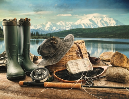 fishing bait: Fly fishing equipment on deck with beautiful view of a lake and mountains Stock Photo