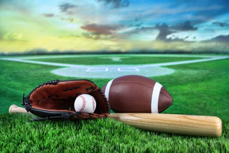 baseball field: Baseball, bat, and mitt with field in background at sunset