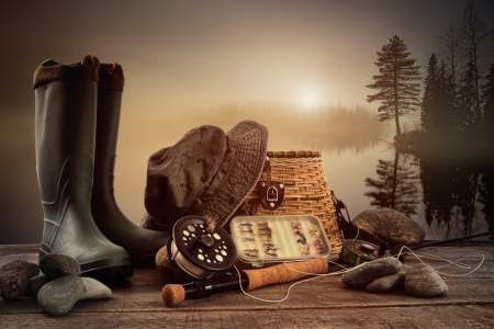 fishing tackle: Fly fishing equipment on deck with view of a misty lake background