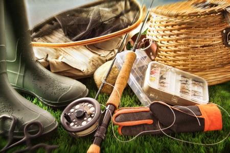 釣り: ブーツおよび草の上のフライフィッシング装置