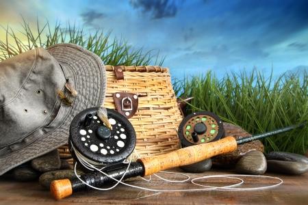 pesca: Equipo de pesca con mosca con el sombrero en el muelle de madera en la hierba