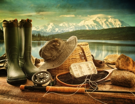 fishing tackle: Fly fishing equipment on deck with beautiful view of a lake and mountains Stock Photo