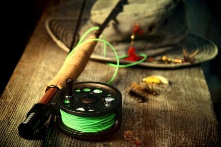 pesca: Equipo de pesca con mosca con el sombrero viejo en el banco Foto de archivo