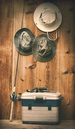 fishing tackle: Hats hanging on wooden wall with fishing equipment
