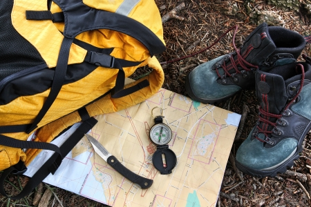 Hiking shoes on map with compass and backpack