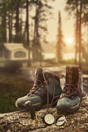 hiking boots: Hiking boots with compass on tree trunk at campsite