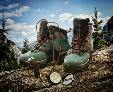 Pair of hiking boots with compass on fallen tree trunk 스톡 콘텐츠