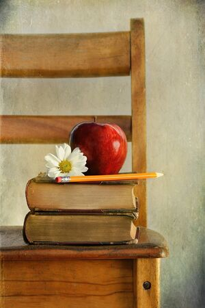 red chair: Red apple and books on old school chair Stock Photo